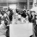 This picture was taken in the years just before World War I an shows immigrants having lunch at Ellis Island. (AP/Press Association).