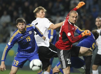 Kazakhstan's Viktor Dmitrenko, left, Austria's Sebastian Prodl, center, and Kazakhstan's goalkeeper Sergei Ostapenko, right, struggle for the ball.