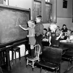Three Finnish children write America on the chalk board in a class held for children of immigrants detained at Ellis Island on 7 April, 1949. They range in ages 3 to 11 years old. (AP Photo)
