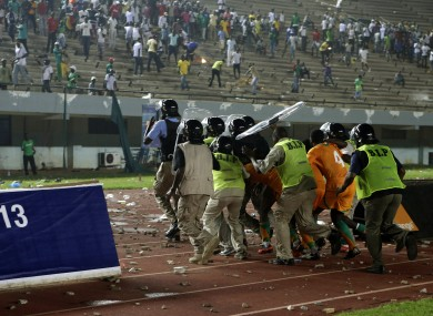 Kolo Toure (4) is among a group of Ivory coast players protected by riot police.