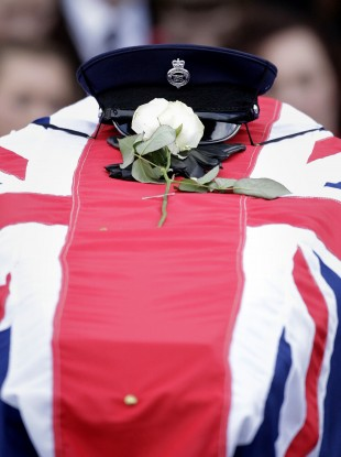 The hat and gloves of murdered prison officer David Black rests on his coffin