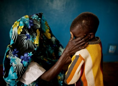 A victim of mass rape and her son in the town of Fizi, Democr