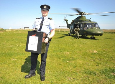 Garda Eugene Organ carrying a ballot box to the polling station on Tory island for the fiscal compact referendum earlier this year.