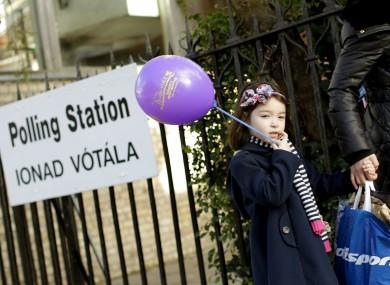 Sinead Yang Yang Glynn, aged four, passes a polling station in Ranelagh, Dublin with her mother Dan Dan Glynn yesterday.