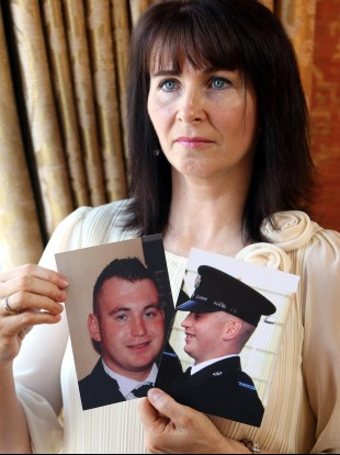Nuala, mother of murdered Constable Ronan Kerr, holds photos of Ronan during an interview with the Press Association