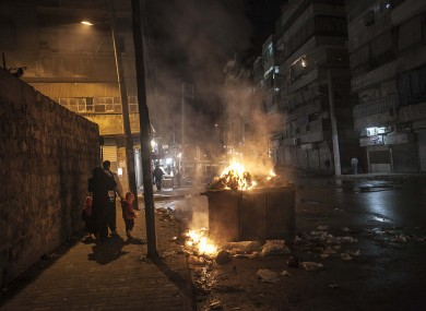 People pass burning garbage on a street in the rebel-controlled part of Aleppo in Syria on Monday