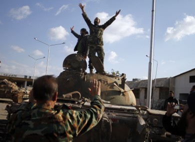 Syrian fighters celebrate victory on top of a tank after storming a military base in Aleppo