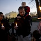 Next to his wife wife Fabiola Cordova, left, Chris Homan of Bethesda, Md., holds his son Leo, 2, on his shoulders while attending a candlelight vigil in front of the White House in Washington yesterday (AP Photo/Jacquelyn Martin).
