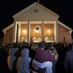 As hundreds stand outside St Rose of Lima Roman Catholic Church, which was filled to capacity, a couple embrace during a  service held in for victims of the elementary school shooting. (AP Photo/Charles Krupa)