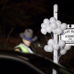 White balloons decorate the sign for the Sandy Hook Elementary School as a Connecticut State Trooper stands guard at the school's entrance. (AP Photo/David Goldman)