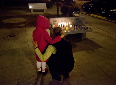 Rhonda Eleish embraces her daughter Kari, 6, next to a candlelight vigil outside Edmond Town Hall in Newtown. Eleish
