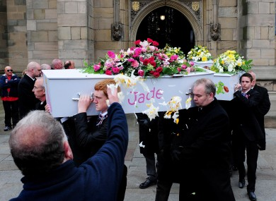 A mourner throws flower petals as coffins leave the funeral service of the Philpott children held at St Mary's RC Church on Bridgegate, Derby on 22 June.