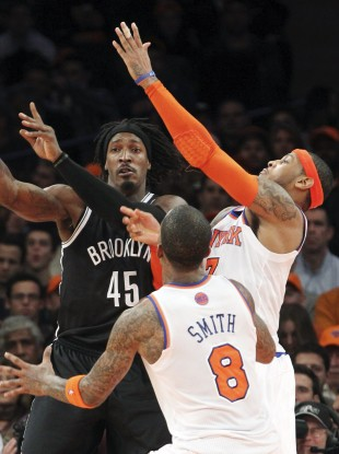 Brooklyn Nets' Gerald Wallace (45) fights for a loose ball against New York Knicks' J.R. Smith (8) and Carmelo Anthony during the first half of their game Wednesday night.