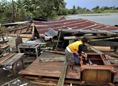 Residents assess their house which was damaged by Typhoon Bopha today.