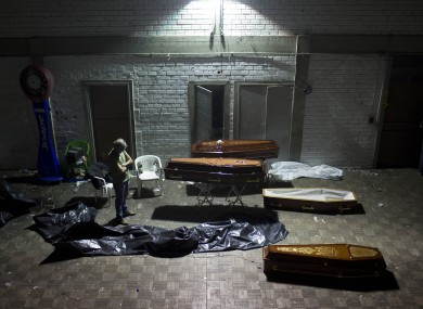 A man stands around coffins containing the remains of victims in Brazil.