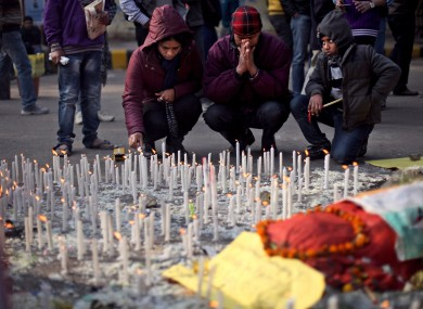 An Indian family lights candles in memory of a gang-rape victim in New Delhi, India, Saturday