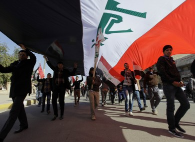 Protesters chant pro-Iraqi Prime Minister Nouri al-Maliki slogans as they carry a huge Iraqi flag during a demonstration to show support for Al-Maliki's government, in Baghdad, last Saturday.
