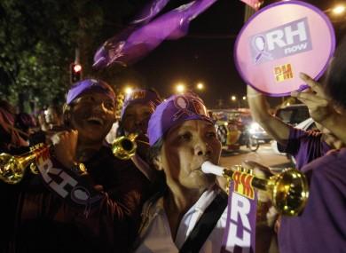 Filipino women celebrate after hearing news that Philippine legislators passed a landmark law