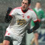 The snow makes an apperance. Tyrone's Plunkett Kane bags a goal despite the Arctic weather in the Athletic Grounds.