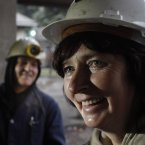 Sakiba Colic, left, and Semsa Hadzo, right,  exchange jokes and laugh outside the shaft of the coal mine in Breza, 20 kms north of Sarajevo, Bosnia, after completing their 8-hour shift.