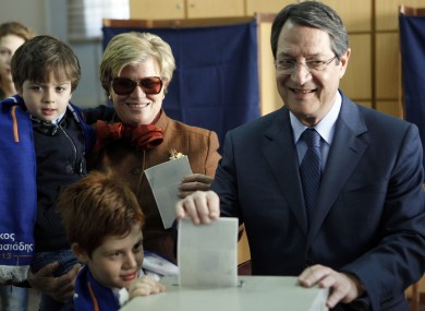 Right-wing opposition leader and presidential candidate Nicos Anastasiades votes with his grandchildren and wife Andriana.