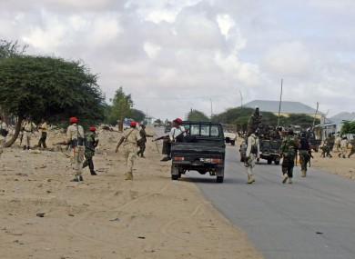 Somali government soldiers take position during a clash with suspected Al -Shabab fighters.
