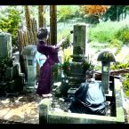 Two people visit a family tomb in a rural cemetery. Flickr/Rob Oeschle (originally T. Enami)