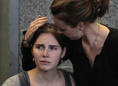 Amanda Knox is hugged by her sister Deanna shortly after arriving in Seattle after her conviction was thrown out