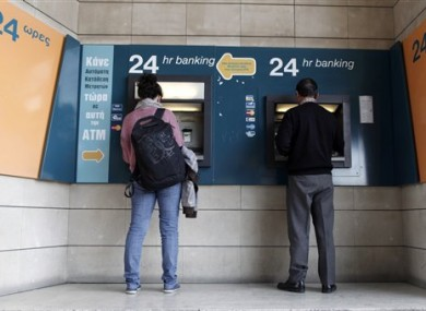 People use ATMs outside a closed branch of the Bank of Cyprus in capital Nicosia.