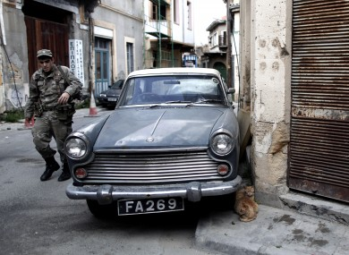 A Greek Cypriot soldier walks at the old town of the capital Nicosia, on Friday, March 29, 2013. Banks in Cyprus are open for normal business for the second day, but with strict restrictions on how much money their clients can access, after being shut for nearly two weeks.