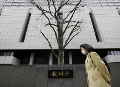 A woman walks by Tokyo District Court during a trial of 19-year-old Richard Hinds of Memphis.