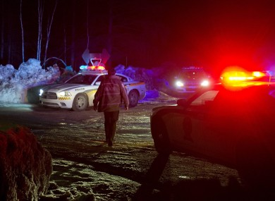 Police vehicles block a road just outside the town of Chertsey, Quebec, Sunday, on Sunday, during a search for escaped prisoners.