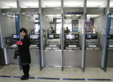 A customer stands in front of ATMs at a branch of Shinhan Bank in Seoul, after the bank's computer networks were paralysed in a suspected attack.