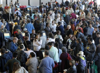 Passengers gather at the American Airlines check-in for flights at Los Angeles International Airport.