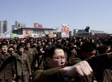 North Koreans punch the air during a rally in North Korea on 29 March in support of their Kim Jong Un's call to arms.