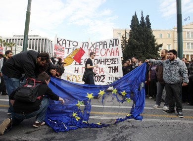 Young Greek people burn an EU flag late last month outside parliament in Athens at protests against education cuts.