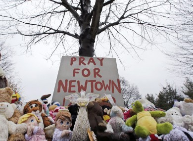 Stuffed animals and a sign calling for prayer sit at the base of a tree near the Newtown VIllage Cemetery in Newtown, Connecticut, after 26 people were shot to death at Sandy Hook Elementary School (file photo).