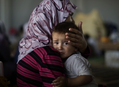 Amjad Al-Saleh, whose family fled to Turkey to escape the violence, is comforted by his mother.