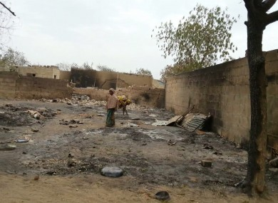 A young girl stands amid the burned ruins of Baga, Nigeria, on Sunday