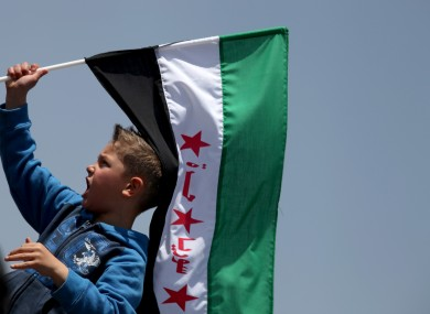 A boy waves the Syrian revolutionary flag as protesters chant anti-Bashar Assad slogans and pro-Jabhat al-Nusra and Free Syrian Army slogans, in front of the Syrian embassy, in Amman, Jordan, last Friday.