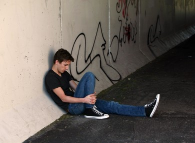 Teen boy sitting in alley (posed by model)