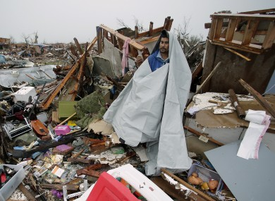 Victor Gonzalez seeks shelter from the rain under a sheet of plastic as he helps a friend salvage items from a tornado-ravaged home.