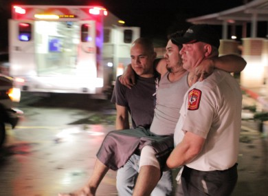 Johnny Ortiz, left, and James South, right, carry Miguel Morales, center, who was injured in a tornado, to an ambulance in Granbury, Texas, on Wednesday May 15, 2013.