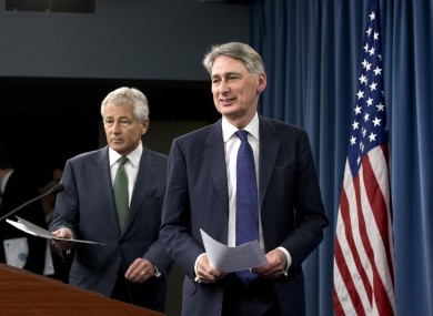 Defense Secretary Chuck Hagel follows British Defense Secretary Philip Hammond for their joint news conference the Pentagon, Thursday, May 2, 2013, where they answered questions on Syria.