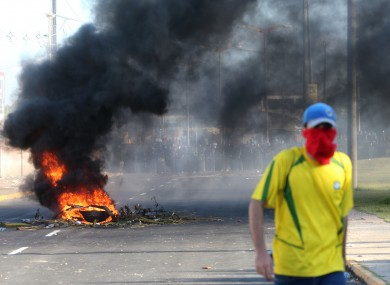 A masked protestor walks near a burning barricade as riot police stand guard near the Castelao stadium in Fortaleza, Brazil.
