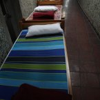Beds line a hallway in the indoor stadium Estadio Victor Jara that opens its doors to the homeless in the evenings during the winter season in Santiago, Chile. Just around the bend is the locker room where famous Chilean folk singer Victor Jara was tortured and killed just days after the bloody military coup that ousted President Salvador Allende. (AP Photo/Brittany Peterson)