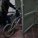 A man staying at the homeless shelter at the indoor stadium Estadio Victor Jara rolls his bike toward the men's bedrooms beneath the stadium, as a soldier guards the door, in Santiago, Chile.  Just days after Chile's bloody 1973 military coup, Victor Jara was dragged down to the basement of this indoor stadium that had been turned into a detention and torture center. Today the stadium is named after him, and is Chile's largest homeless shelter, housing about 500 people per day during the biting Chilean winter. (AP Photo/Brittany Peterson)
