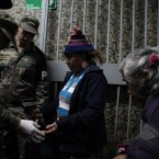 A woman opens her bag for soldiers to search through before entering a homeless shelter at the indoor stadium Estadio Victor Jara in Santiago, Chile. The stadium, which opened its doors on May 15 as a temporary shelter to house people throughout the winter who normally sleep on the streets, is where Chilean folksinger Victor Jara was tortured and killed in 1973, just days after Chile's bloody 1973 military coup. (AP Photo/Brittany Peterson)