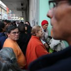 """Ana Luisa Villarroel, 78, center right, waits in line to be one of the first to enter the homeless shelter at the indoor stadium Estadio Victor Jara in Santiago, Chile. This is her first night at the shelter after she left what she described as an abusive situation at her family's home. This emblematic stadium, which hosts sporting events throughout the year, was where Chilean folk singer Victor Jara was tortured and killed on Sept. 14, 1973, just days after the military coup. """"For me, it's a miracle to be here where they are now giving shelter and food to everyone and where they killed Victor Jara,"""" said Ana Luisa Villaroel, 78, who lived through the dictatorship. (AP Photo/Brittany Peterson)"""