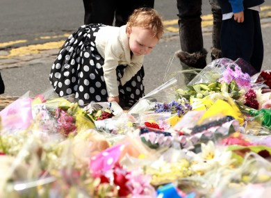 Two year old Ruby Kent from Hampton Court lays flowers outside the Royal Artillery Barracks, in Woolwich, east London close to the scene where Drummer Lee Rigby was murdered.